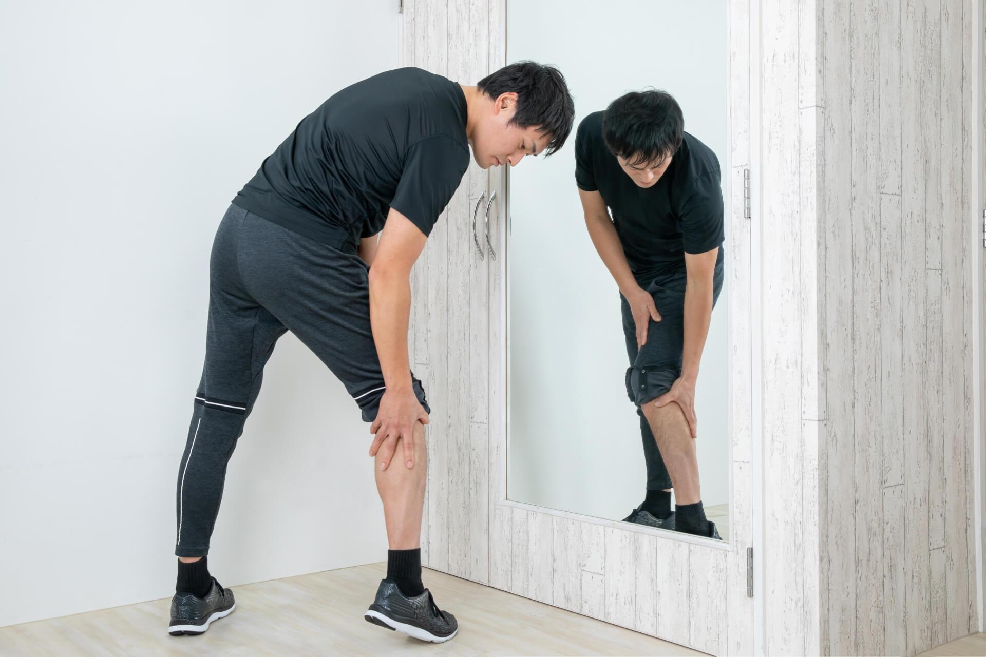 男性が脛を抑えている写真