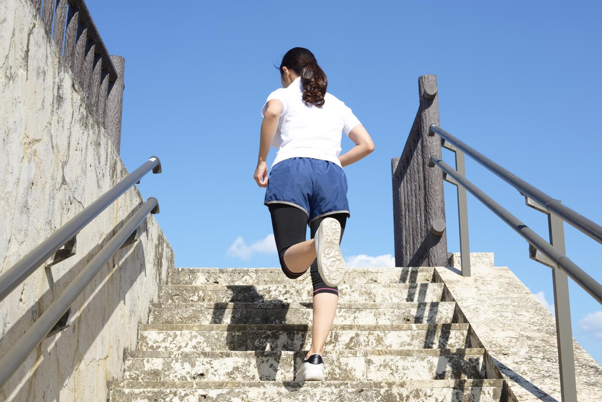女性が階段を駆け上がる写真